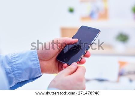 Businessman using mobile phone at modern stylish office - stock photo