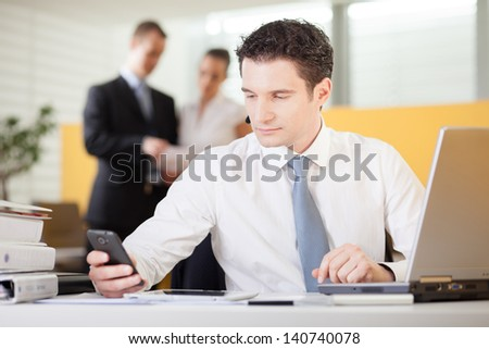 Businessman using mobile phone in an office - stock photo