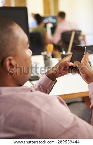 Businessman Using Mobile Phone In Creative Office - stock photo