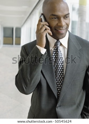 Businessman using mobile phone in hallway