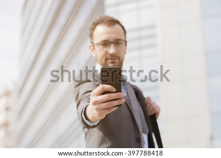 Businessman using mobile phone in the front of the business building. He is wearing suit an have the laptop bag over his shoulder  - stock photo