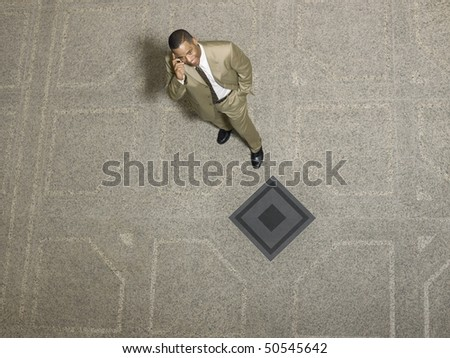 Businessman using mobile phone, indoors - stock photo
