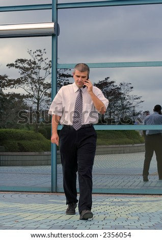 Businessman using mobile phone while is walking in hurry in front of a blue corporate building.