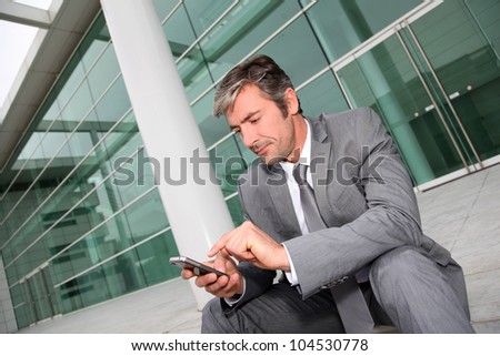 Businessman using mobile phone while seated in stairs - stock photo