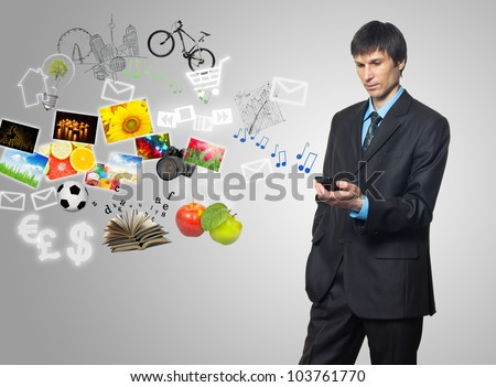 Businessman using mobile phone with touch screen with streaming images, email, multimedia symbols - stock photo