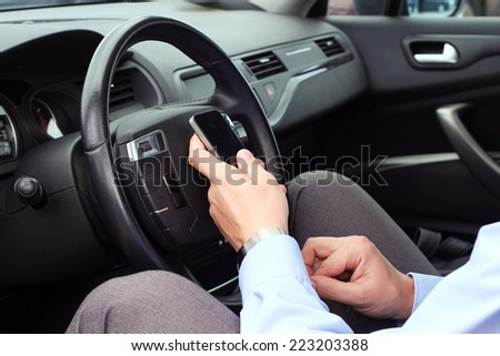 businessman using  mobile smart phone while driving the car - stock photo