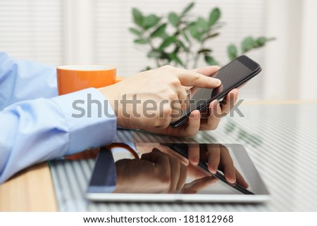 Businessman using  modern mobile phone and digital tablet computer - stock photo