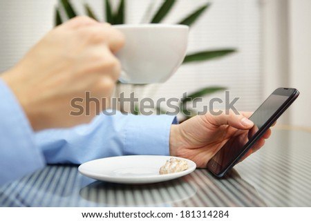 Businessman using  modern mobile phone and drinking coffee. Mobile technologies for successful work flow concept - stock photo