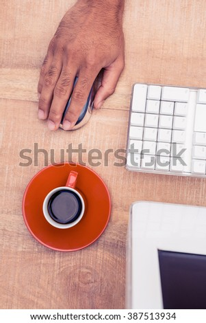 Businessman using mouse by coffee cup while working at desk in office - stock photo