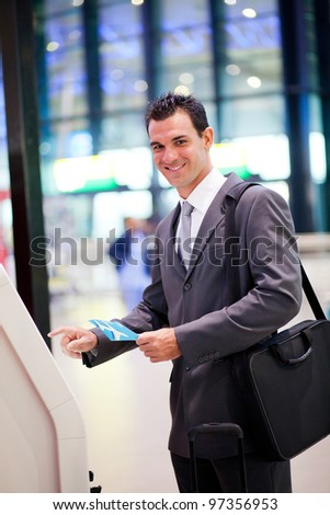 businessman using self help check in machine at airport