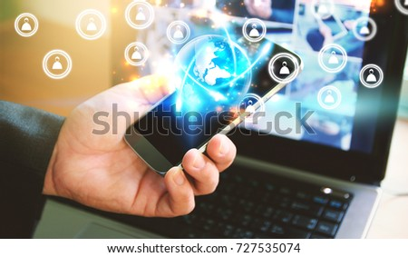 Businessman using smart phone and computer.