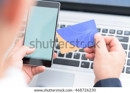 Businessman using smart phone and credit card for paying online.