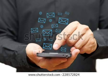 Businessman using smart phone with email icons around - stock photo