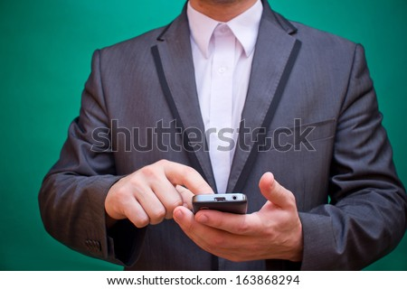 Businessman using smartphone typing and reading in suit - stock photo