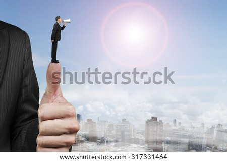 Businessman using speaker shouting on another man big hand thumb, with sun sky clouds cityscape background.