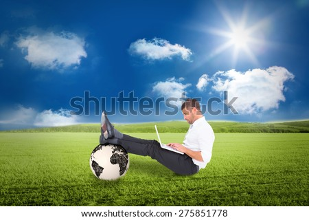 Businessman using tablet against sunny green landscape - stock photo