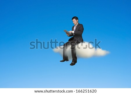 Businessman using tablet and sitting on cloud in sky background - stock photo