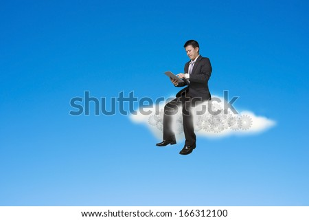 Businessman using tablet and sitting on cloud with gears inside, in sky background
