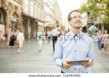 Businessman Using Tablet Computer in public space - stock photo