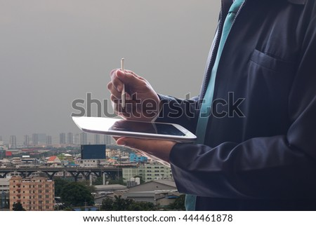 Businessman using tablet computer with city background