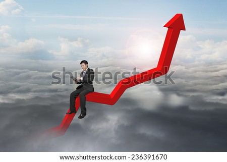 businessman using tablet on red trend chart with natural sky daylight cloudscape background - stock photo
