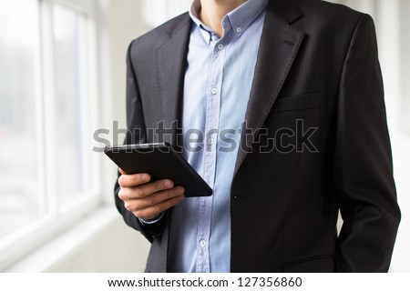 Businessman using tablet pc and works on it - stock photo