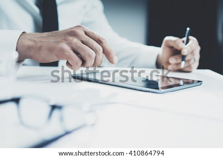 Businessman using tablet pc at his office, male doctor using modern digital tablet, documents and glasses on the desktop