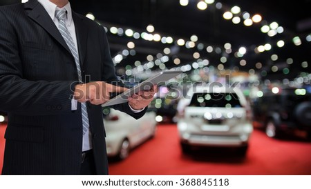 businessman using tablet with blurred event background