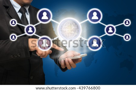 Businessman using the smart phone with the Social media symbol on blue color background with world map,Elements of this image furnished by NASA, Business network concept
