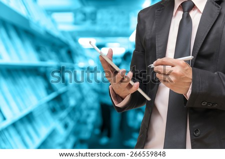Businessman using the tablet on Abstract blurred photo of book store background, blur color tone - stock photo