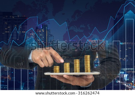 Businessman using the tablet with stack of golden coins on Trading graph on the cityscape at night ,Business financial concept
