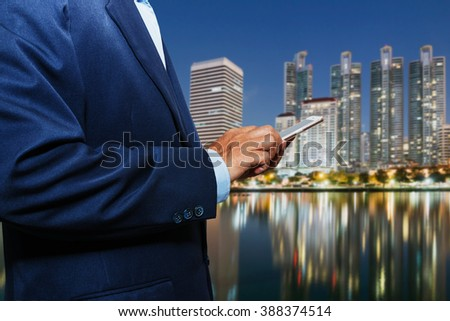 Businessman using touch screen mobile smart phone on city night blur background