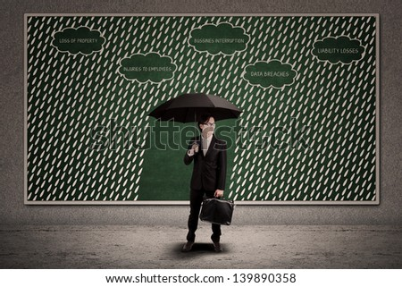 Businessman using umbrella to protect business loss under the rain - stock photo