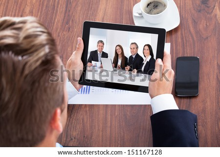Businessman Video Conferencing On Digital Tablet In Office - stock photo
