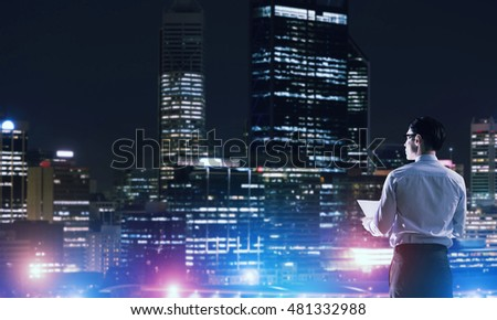 Businessman viewing night glowing city
