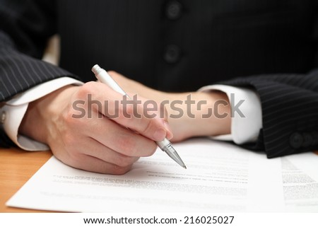 Businessman viewing the contract before signing.