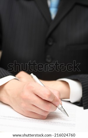 Businessman viewing the contract before signing. Focus on pen. Closeup.