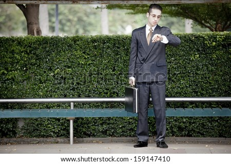 businessman waiting at the bus stop,clean city concept. - stock photo