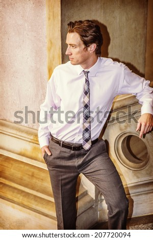 Businessman Waiting for You. Dressing in a white shirt, patterned neck tie,  gray pants, a young businessman is standing by a railing, looking away, relaxing. - stock photo