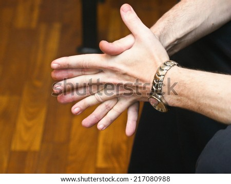 Businessman waiting with folded hands, isolated on dark - stock photo