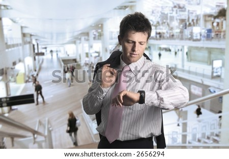 Businessman waits for a meeting in a huge entrance hall. - stock photo