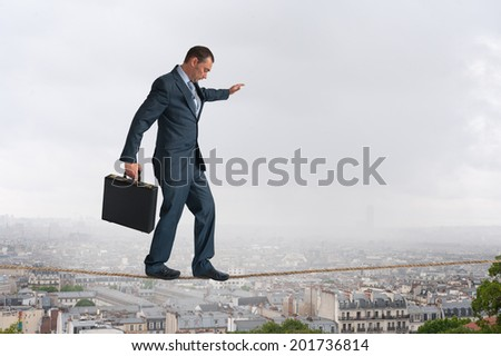 businessman walking across a tightrope above the city - stock photo