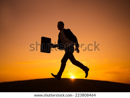 Businessman Walking Across the Hill - stock photo