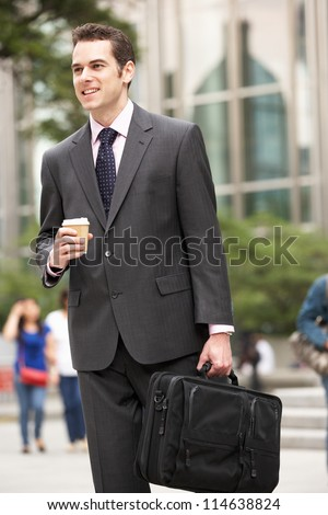 Businessman Walking Along Street Holding Takeaway Coffee - stock photo