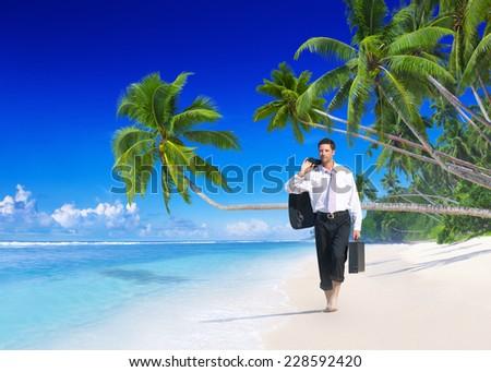 Businessman walking along the beach. - stock photo
