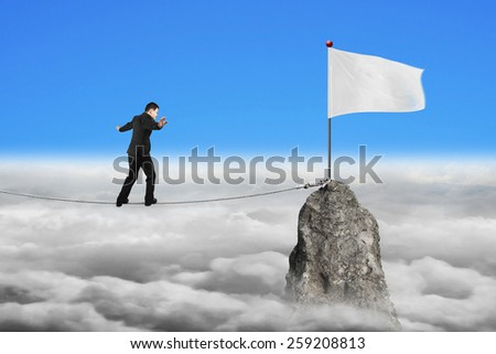 Businessman walking and balancing on rope toward white flag of mountain peak with cloudscape background