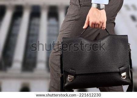 Businessman walking and holding  a  leather briefcase in his hand.  Modern city behind  - stock photo
