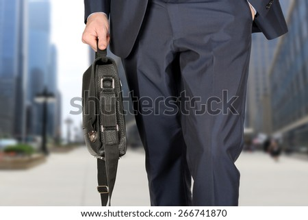 Businessman walking and holding  a  leather briefcase in his hands Modern city behind  - stock photo