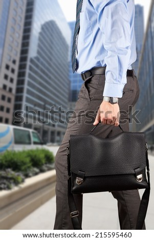 Businessman walking and holding  a  leather briefcase in his handss Modern city behind  - stock photo