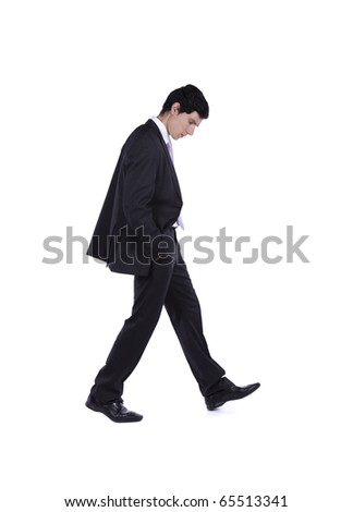 Businessman walking and looking down isolated on white (some motion blur)